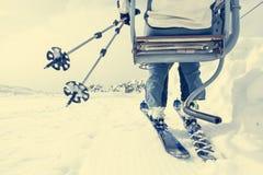 Achtermening van skiër die een lift berijden Stock Afbeelding