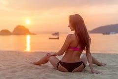 Achtermening van slanke vrouwelijke modelzitting op kust die bikini dragen die weg tijdens zonsopgang kijken met weerspiegelde zo stock fotografie