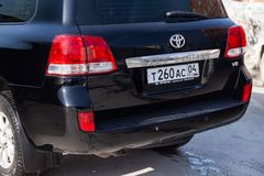 Achtermening van Toyota Land Cruiser 200 in zwarte kleur na het schoonmaken vóór verkoop in een zonnige dag op parkeren stock afbeeldingen