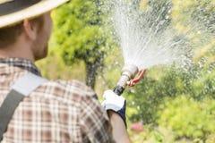 Achtermening van tuinman het water geven installaties bij tuin Royalty-vrije Stock Fotografie