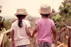 Achtermening van twee hand houden en meisjes die samen lopen stock foto