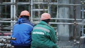 Achtermening van twee ingenieursbouwers bij bouwwerf het leiden klem Twee arbeiders in een achtermeningshelm stock videobeelden