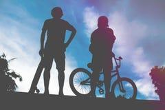 Achtermening van twee jonge mensen bmx fiets en skateboard stock afbeelding