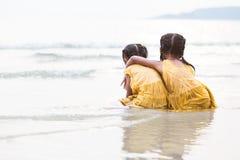 Achtermening van twee leuke Aziatische kleine kindmeisjes die op strand koesteren royalty-vrije stock foto