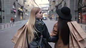 Achtermening van twee lopende vrouwen met het winkelen zakken stock video
