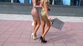Achtermening van twee lopende vrouwen met het winkelen zakken Slow-motion close-up van vrouwelijke benen in hoge hielen Close-up  stock video