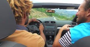 Achtermening van twee mensen die terwijl het drijven in convertibel op kustweg partying stock videobeelden