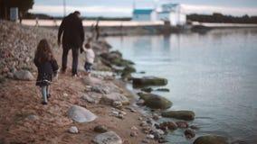 Achtermening van vader en zoon die langs de kust, dochterlooppas aan hen lopen Broer en zuster het besteden tijd met papa stock footage