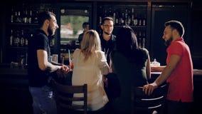 Achtermening van vier jonge vrienden die bij bar het tegen spreken met barman aan de andere kant van houten lijst ontspannen bedr stock footage