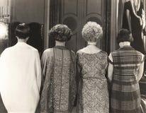 Achtermening van vier vrouwen die zich op een rij bevinden stock afbeeldingen