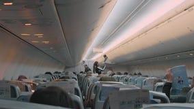 Achtermening van vliegtuigraad tijdens vlucht De mensen zitten op stoelen die het letten lezen op en aan muziek luisteren stock videobeelden