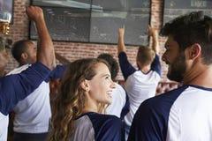 Achtermening van Vrienden die op Spel in Sportenbar letten op de Schermen stock foto's
