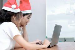 Achtermening van vrolijke jonge Aziatische vrouwen die in Kerstmanhoeden online met laptop in woonkamer thuis winkelen Vrolijke K royalty-vrije stock fotografie