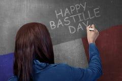 Achtermening van vrouw die gelukkige bastilledag op de muur schrijven royalty-vrije stock afbeeldingen