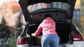 Achtermening van vrouw die het winkelen zakken in auto zetten stock footage