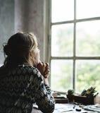 Achtermening van vrouw die nadenkend vooruitzicht van het venster zitten stock foto's