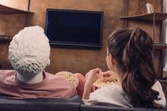 achtermening van vrouw die popcorn eten terwijl het letten van op film samen met mannequin thuis perfecte verhouding stock foto