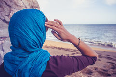 Achtermening van vrouw met headscarf die het overzees bekijken royalty-vrije stock foto's