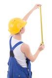 Achtermening van vrouwenbouwer in blauwe overtrekken die iets meten stock foto
