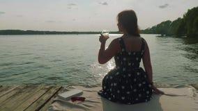 Achtermening van vrouwenzitting op oude pijler De vrouw neemt glas witte wijn, drinkt het, en zet achter het stock footage
