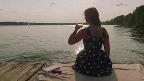 Achtermening van vrouwenzitting op oude pijler Het vrouwen atakes glas wijn, drinkt het, en zet achter het stock video
