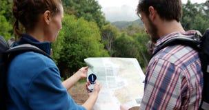 Achtermening van wandelaars die een kaart met een kompas kijken stock videobeelden