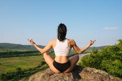 Achtermening van yogavrouw met het perfecte spierlichaam mediteren in lotusbloemhouding op de rots Berglandschap en blauw royalty-vrije stock foto's