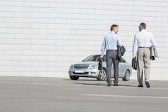Achtermening van zakenlieden die aktentassen dragen terwijl het lopen naar auto op straat royalty-vrije stock foto