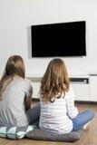 Achtermening van zusters die op TV thuis letten Royalty-vrije Stock Fotografie
