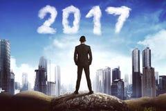 Achtermenings bedrijfsmens die de wolk van 2017 op de hemel kijkt Royalty-vrije Stock Foto's