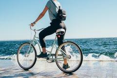 Achtermenings jonge vrouw die tijdens fietsrit wordt tegengehouden stock afbeelding