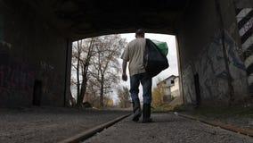 Achtermenings werkloze mens die met vuilniszakken loopt stock videobeelden