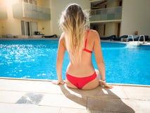 Achtermeningsbeeld van mooie sexy jonge vrouw in rode bikinizitting op poolside bij hoteltoevlucht Vrouw het ontspannen en royalty-vrije stock afbeeldingen