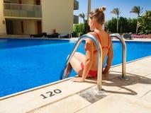 Achtermeningsbeeld van mooie sexy jonge vrouw in rode bikinizitting op poolside bij hoteltoevlucht Vrouw het ontspannen en stock fotografie