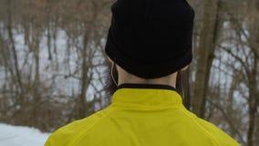 Achtermeningsclose-up van de gebaarde mens met oortelefoons die zich in de winterbos bevinden stock videobeelden