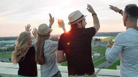 Achtermeningsgroep die mensen van mooi stadslandschap genieten die wapens op dakpartij opheffen bij zonsondergang stock video