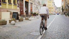 Achtermeningslengte van modieuze jonge personenvervoerfiets op oude bedekte weg stock video