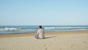 Achtermeningsportret van de één mens die op de overzeese zitting op het zand van het strand letten stock video