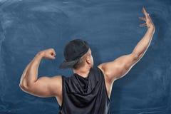 Achtermeningsportret van een geschikte atleet verbuiging en het uitrekken zich wapenspieren op de donkerblauwe achtergrond Stock Foto