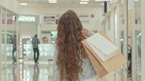 Achtermeningsschot van een krullend haired meisje die kledingsopslag bekijken bij winkelcomplex stock footage