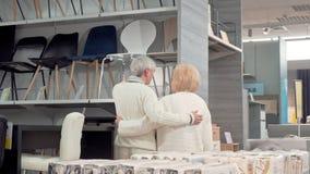 Achtermeningsschot van een mooi hoger paar die meubilair kiezen samen bij de opslag stock footage
