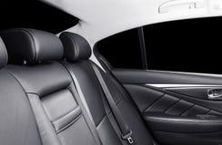 Achterpassagierszetels in moderne luxeauto Frontale mening Zwart geperforeerd leer met het witte stikken Auto het detailleren Lee stock foto