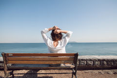 Achterportret van Vrouw met krullende haarzitting op een bank Vrouw in wit overhemd, zonnige dag, gelukkig, aantrekkelijk denken, Royalty-vrije Stock Afbeeldingen
