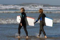 Achtersurfers die in de oceaan gaan royalty-vrije stock afbeelding