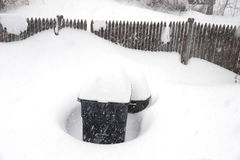 Achtertuinomheining en afvalbak in blizzard royalty-vrije stock afbeelding