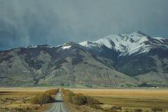 Achteruitgaande geteerde weg in een bergachtig landschap stock foto's