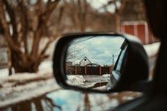 Achteruitkijkspiegel die de omheining en het huis overzien gekleurd stock foto's