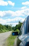Achteruitkijkspiegel van de auto die zich op een kant van de weg bevinden Stock Foto's