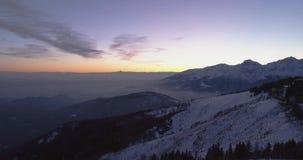Achterwaartse lucht hoogste mening over de winter sneeuwberg met auto die op weg reizen Blauwe van de uurschemer of dageraad sche stock footage