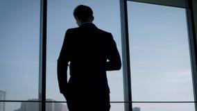 Achterweergeven van Zakenman In Suit Standing in Bureau die uit het Venster kijken stock video